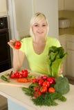 Junge blonde Frau mit Gemüse auf Küche Stockfotos
