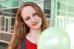 Junge blonde Frau mit grünem Ballon Stockfotos