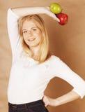 Junge blonde Frau mit grünem und rotem Apfel, gute Wahl, Diätkonzept, Lebensstilgesundheitswesenleute Stockfoto