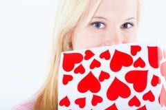 Junge blonde Frau mit großer Valentinsgrußpostkarte Lizenzfreie Stockfotos