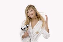 Junge blonde Frau mit hairdryer Stockfoto