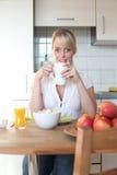 Junge blonde Frau mit ihrem Frühstück Lizenzfreie Stockbilder