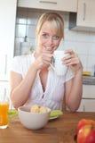 Junge blonde Frau mit ihrem Frühstück Lizenzfreie Stockfotografie