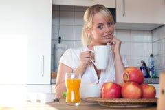 Junge blonde Frau mit ihrem Frühstück Stockfotografie