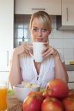 Junge blonde Frau mit ihrem Frühstück Stockbild