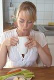 Junge blonde Frau mit ihrem Frühstück Lizenzfreies Stockfoto