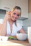 Junge blonde Frau mit ihrem Frühstück Lizenzfreie Stockfotos