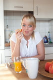 Junge blonde Frau mit ihrem Frühstück Stockbilder