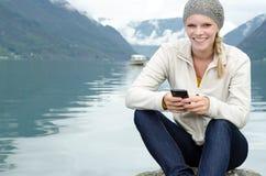 Junge blonde Frau mit ihrem Smartphone in der Hand Lizenzfreie Stockbilder