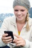 Junge blonde Frau mit ihrem Smartphone in der Hand Lizenzfreies Stockfoto