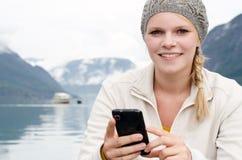 Junge blonde Frau mit ihrem Smartphone in der Hand Lizenzfreie Stockfotografie