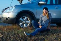 Junge blonde Frau mit ihrem unterbrochenen Auto Stockfoto