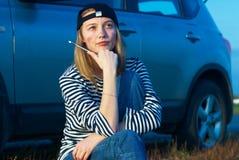 Junge blonde Frau mit ihrem unterbrochenen Auto Stockbilder