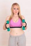 Junge blonde Frau mit ihren Gewichten Lizenzfreies Stockbild
