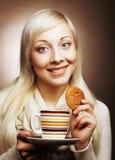 Junge blonde Frau mit Kaffee und Plätzchen Stockbilder