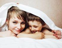 Junge blonde Frau mit kleinem Jungen im Bett, der Mutter und Sohn, glücklich Stockfotografie