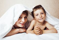 Junge blonde Frau mit kleinem Jungen im Bett, der Mutter und Sohn, glücklich Stockbild