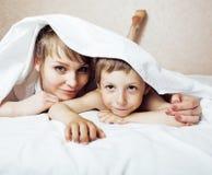 Junge blonde Frau mit kleinem Jungen im Bett, der Mutter und Sohn, glücklich Stockfotos