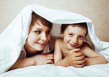 Junge blonde Frau mit kleinem Jungen im Bett, der Mutter und Sohn, glücklich Lizenzfreie Stockfotos