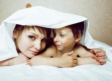 Junge blonde Frau mit kleinem Jungen im Bett, der Mutter und Sohn, glücklich Lizenzfreie Stockbilder