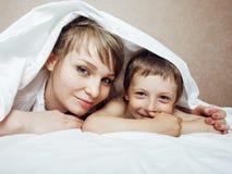 Junge blonde Frau mit kleinem Jungen im Bett, Mutter und Sohn, glückliche Familie Stockfotos