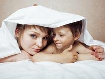 Junge blonde Frau mit kleinem Jungen im Bett, Mutter und Sohn, glückliche Familie Lizenzfreie Stockbilder