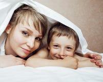 Junge blonde Frau mit kleinem Jungen im Bett, Mutter und Sohn, glückliche Familie Lizenzfreies Stockfoto