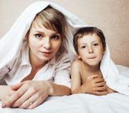 Junge blonde Frau mit kleinem Jungen im Bett, Mutter und Sohn, glückliches familyyoung blonde Frau mit kleinem Jungen im Bett, Mu Stockfotos