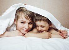 Junge blonde Frau mit kleinem Jungen im Bett, Mutter und Sohn, glückliches familyyoung blonde Frau mit kleinem Jungen im Bett, Mu Stockbilder