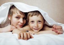 Junge blonde Frau mit kleinem Jungen im Bett, Mutter und Sohn, glückliches familyyoung blonde Frau mit kleinem Jungen im Bett, Mu Lizenzfreie Stockbilder