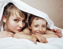 Junge blonde Frau mit kleinem Jungen im Bett, Mutter und Sohn, glückliches familyyoung blonde Frau mit kleinem Jungen im Bett, Mu Stockbild