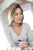 Junge blonde Frau mit Kopfhörern Stockbild