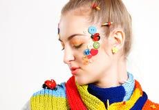 Junge blonde Frau mit Kreativitätsfrisur mit farbigen Knöpfen Stockfotos