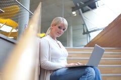 Junge blonde Frau mit Laptop Lizenzfreie Stockbilder
