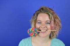Junge blonde Frau mit Lutscher zwischen ihren Zähnen Stockfoto