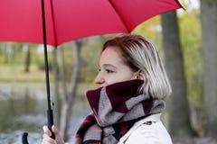 Junge blonde Frau mit Regenschirm Stockfotografie