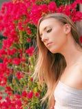 Junge blonde Frau mit roten Blumen im Hintergrund Lizenzfreie Stockfotos