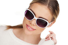 Junge blonde Frau mit sunglases, Studioweiß Stockfoto