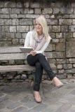 Junge blonde Frau mit Tablette Stockfoto