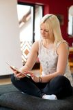 Junge blonde Frau mit Tabletten-PC Lizenzfreie Stockfotografie
