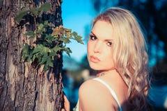 Junge blonde Frau nahe bei einem Baum Lizenzfreie Stockbilder