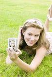 Junge blonde Frau nimmt ein Selbstportrait mit einer Kamera Stockfoto