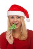 Junge blonde Frau in Sankt-Hut mit Süßigkeit Lizenzfreie Stockfotos