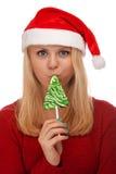 Junge blonde Frau in Sankt-Hut mit Süßigkeit Lizenzfreies Stockfoto