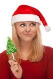Junge blonde Frau in Sankt-Hut mit Süßigkeit Stockfotografie