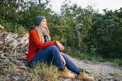 Junge blonde Frau sitzt im Freien auf dem Hintergrund des Waldes Lizenzfreie Stockfotos