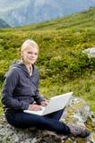 Junge blonde Frau sitzt mit einem Laptop auf einem Stein Stockbild