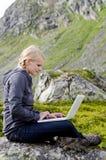 Junge blonde Frau sitzt mit einem Laptop auf einem Stein Stockbilder