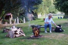 Junge blonde Frau sitzt mit ihrem border collie durch das Lagerfeuer Lizenzfreie Stockfotos