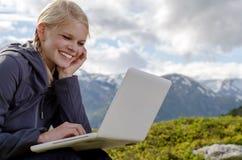 Junge blonde Frau sitzt mit Laptop in der Wiese Stockbild
